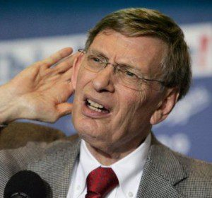 Bud Selig holds his hand to his ear to hear a question.