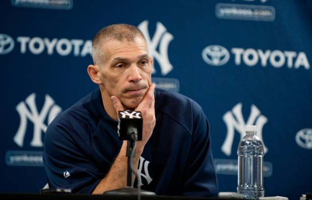 New York Yankees manager Joe Girardi scratches his chin at a press conference.