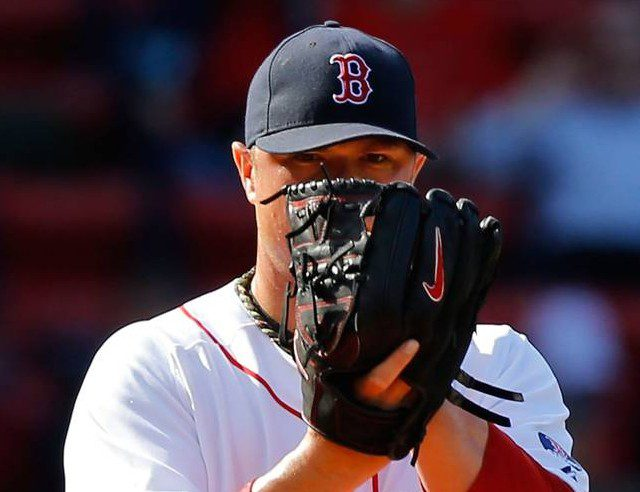 Boston Red Sox pitcher Jon Lester stares over his glove as he prepares to throw a pitch.