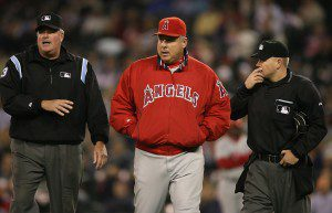 Mike Scioscia walks and talks with two umpires.